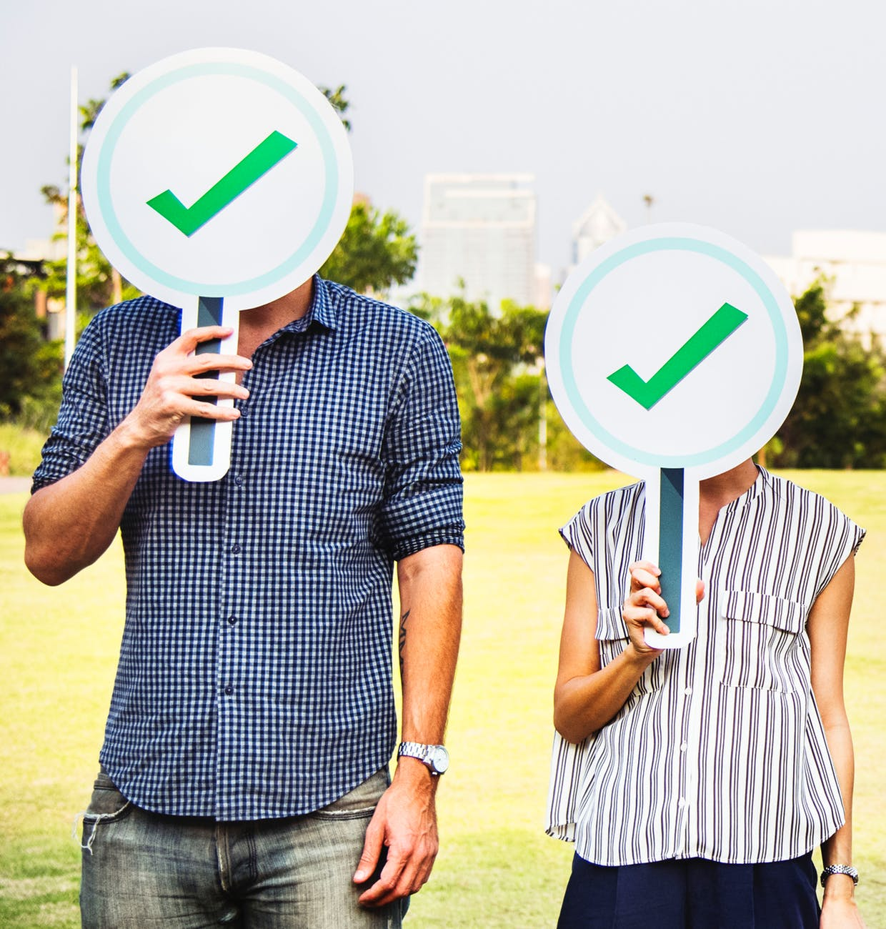 man and woman holding check signage