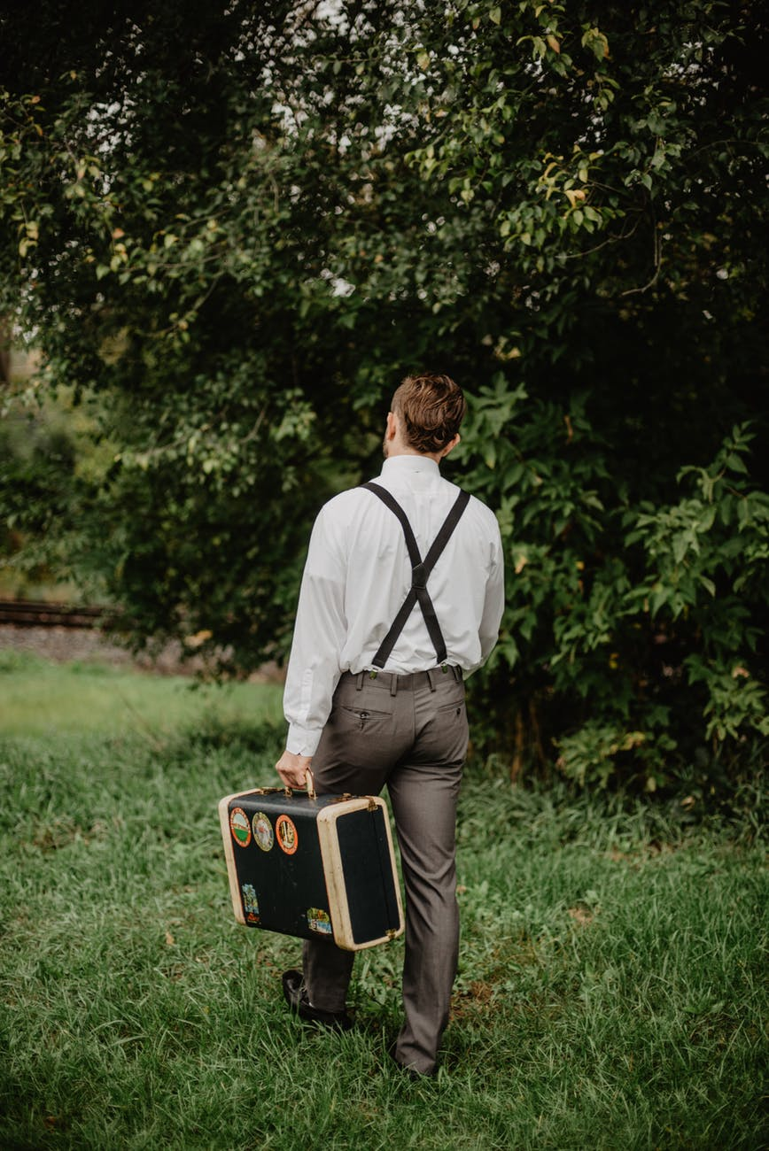 man carrying black and gold briefcase